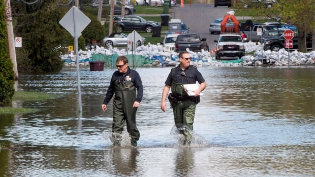 Firefighters walk through a flooded street as the water starts to recede May 12, 2017 in Deux-Montagnes, Que. The city says it needs to build a new permanent dike.