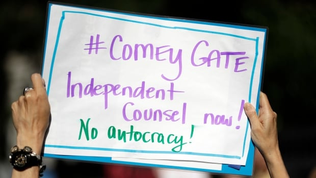 A protester's sign makes the connection between the Watergate scandal and the current scandal involving U.S. President Donald Trump's firing of FBI Director James Comey.