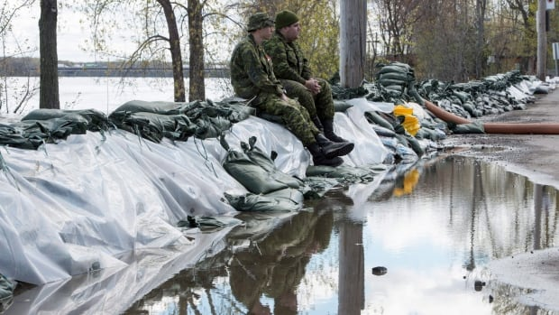 Two soldiers sit on a dam built along the Rivière des Prairies in the Pierrefonds borough of Montreal on Friday. Montreal officials have decided to lift the state of emergency beginning Sunday at noon because water levels are receding rapidly.