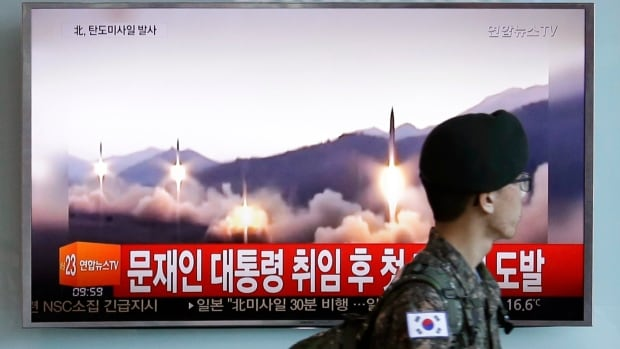 A South Korean army soldier walks by a TV news program showing a file image of missiles being test-launched by North Korea, at the Seoul Railway Station in Seoul on Sunday.