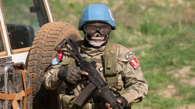 A UN peacekeeping soldier provides security during a food aid delivery in a village in Central African Republic, in April. Canada intends to push other countries to pledge more troops to international operations when it hosts a peacekeeping meeting in November.