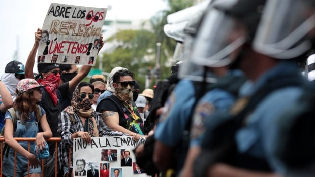 Demonstrators protest against the government's austerity measures in San Juan, Puerto Rico, on May 1. The sign reads: 'Open your eyes, reflect, join us.' The U.S. territory has declared bankruptcy and will be in court Wednesday to try to get out from under its $123 billion US debt.