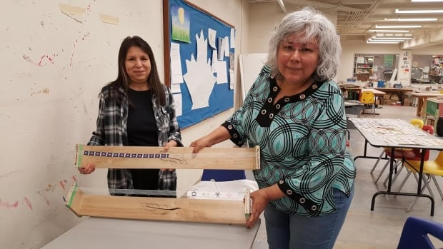 Lisa Neuls, left, and Barb Frazer, right, display partially finished beaded belts the  women have been working on as part of Nato' we ho win, a new program that uses Indigenous cultural traditions to help women heal from domestic violence.