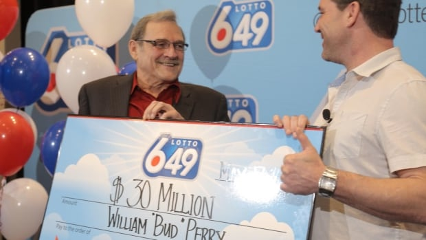 William 'Bud' Perry poses with a cheque for $30 million after winning the May 10 Lotto 6/49 Jackpot.