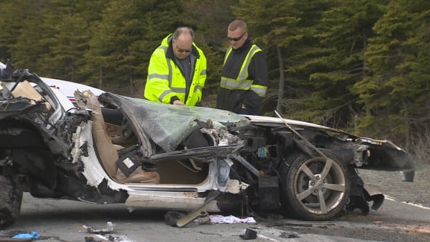 Investigators examine the wreckage of a Corvette on Blackhead Road on Wednesday afternoon after a single-vehicle crash. Two men were sent to hospital with serious injuries.