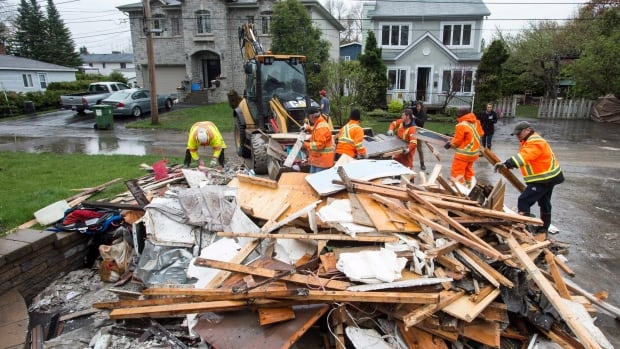 City workers pick up debris removed from a flooded house in the Pierrefonds borough of Montreal.