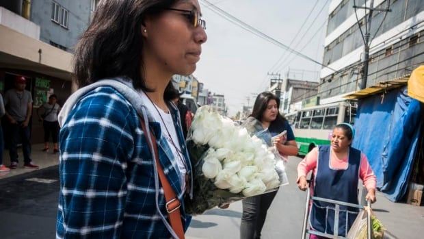 Letty Cruz walks with a bundle of roses to her outreach organization's small office in the La Merced neighbourhood of Mexico City on May 10, Mexico's Mother's Day.  Cruz and her colleagues normally circulate through the neighbourhood distributing condoms to sex workers but on that day, they gave out roses instead.