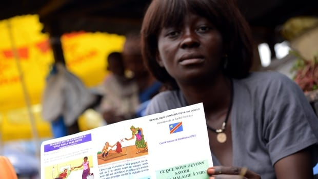 A vegetable seller holds a Congolese Ministry of Health's information leaflet on Ebola virus in 2014. This latest Ebola outbreak is the country's eighth.