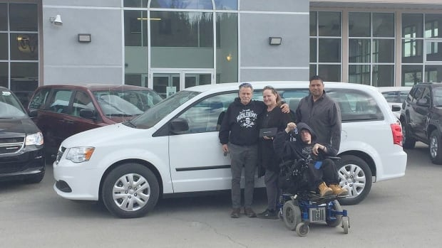 Wayne Thomas with his family and the 2016 Dodge Grand Caravan donated to them by Whitehorse's Metro Chrysler dealership. General sales manager Travor Willier is at right. The van will be made wheelchair-accessible for Thomas.