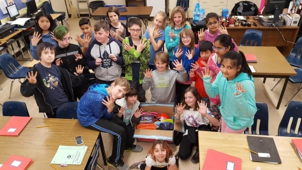 The kids of room 9 show their class pride by holding up 9 fingers as they stand next to a package they intended to mail to Kenya to be delivered to children in South Sudan.