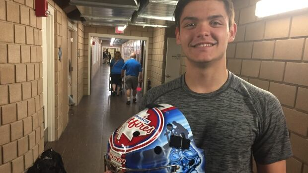 Windsor Spitfire goalie Michael DiPietro holds his mask, which pays tribute to Canada's fallen veterans.  (Jason Viau/CBC News)