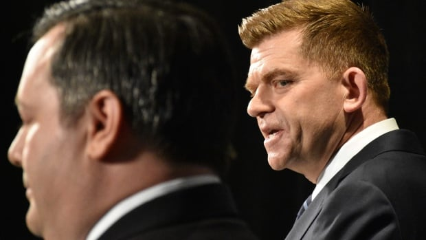 Wildrose Leader Brian Jean looks on as PC Leader Jason Kenney talks Thursday at a news conference to announce an agreement in principle aimed at creating a new United Conservative Party.