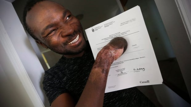 Seidu Mohammed smiles as he shows off his refugee claim acceptance letter in Winnipeg, Thursday, May 18, 2017.