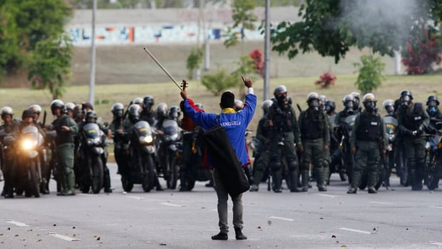 An anti-government protester raises his violin before National Guard members, as he yells not to shoot at protesters, creating a brief pause during clashes in Caracas on Thursday.