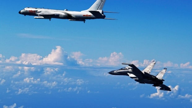 A Chinese People's Liberation Army Air Force SU-30 fighter, right, flies along with a H-6K bomber as they take part in a drill near the East China Sea in this photo released Sept. 25, 2016. On Friday, two Chinese SU-30s intercepted a U.S. aircraft over the East China Sea.