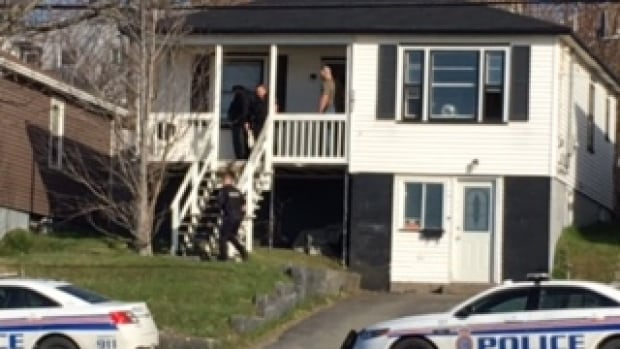 A man is placed in handcuffs outside a home on Empire Avenue Thursday afternoon.