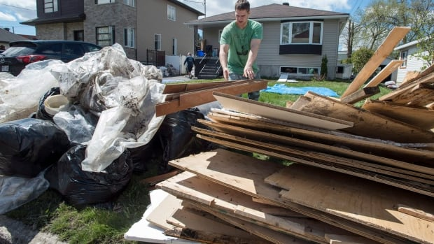 Residents clear debris from their house following a flood in the Pierrefonds borough of Montreal, Friday, May 12, 2017. The Quebec government is compiling resources to help people who have to rebuild.
