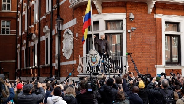 WikiLeaks founder Julian Assange gestures on the balcony of the Ecuadorian embassy prior to speaking, in London, on Friday. Assange took refuge at the embassy to avoid extradition to Sweden over a rape allegation, which he denies.