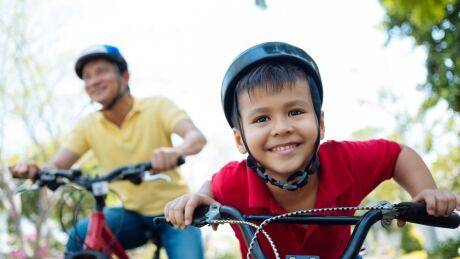 Kid riding bicycle with parent
