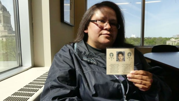 Cynthia Lacquette holds a memorial card made five years after the 2002 murder of her son, James Isaac.