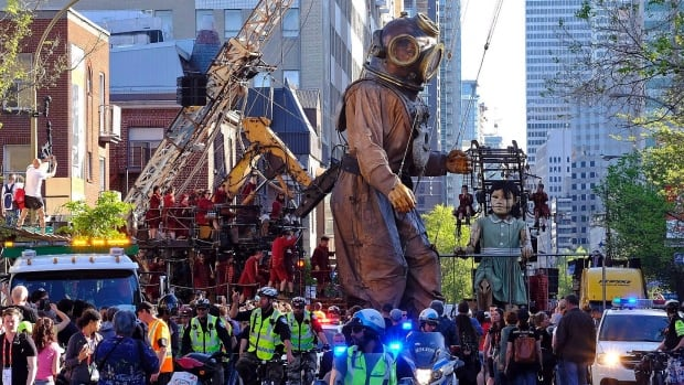 People look on as giant marionettes make their way through the streets of Montreal as part of the city's 375th anniversary celebrations.
