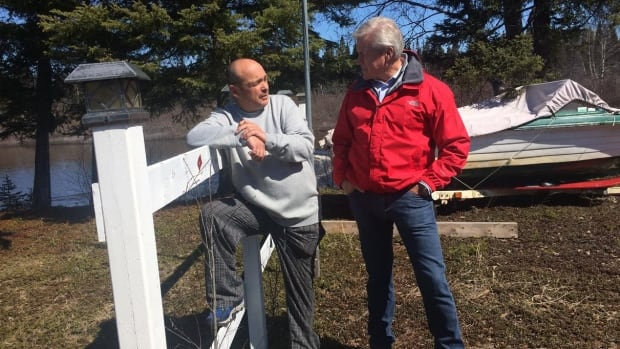 Premier Dwight Ball talks with a resident of Mud Lake after viewing the damage caused by flooding.