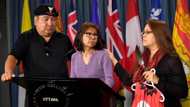 Jocelyn Wabano-Iahtail, right, comforts Shirley Gunner, as John Fox looks on during a news conference regarding the missing and murdered Indigenous women and girls national inquiry in Ottawa.