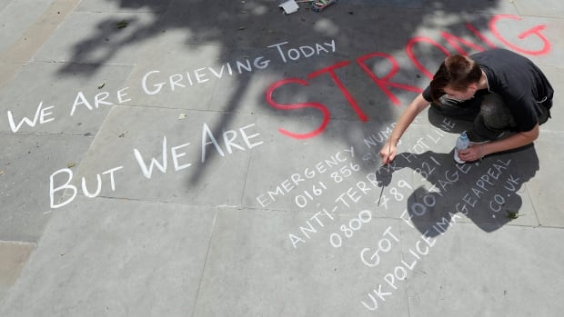 A man writes a message on the pavement in central Manchester following the attack after the concert.