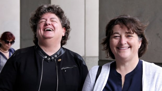 Retired RCMP officers Linda Davidson (left) and Janet Merlo share a laugh outside Federal Court in Toronto last week, before the judge released her decision.