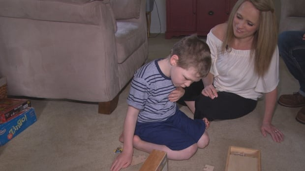 Liam McKnight, left, and his mother, Mandy, put together a puzzle at their home. Mandy McKnight estimates her son's seizures have been reduced by about 90 per cent since he began taking cannabis oil.