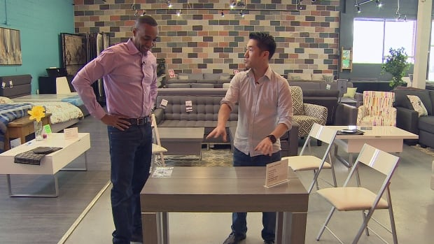 Joseph Duan (right) shows CBC Toronto host Dwight Drummond how condo furniture can be multi-functional to save on space.