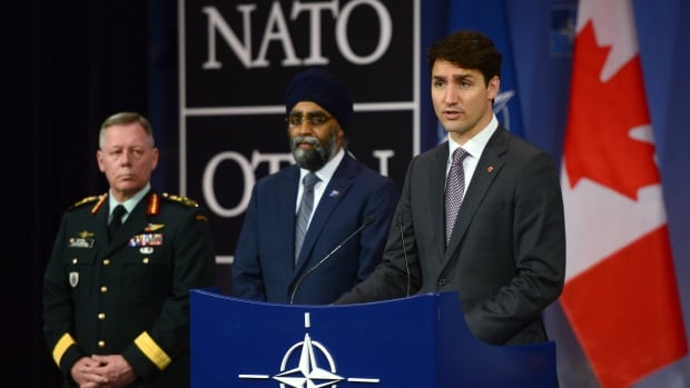 Prime Minister Justin Trudeau stands with Defence Minister Harjit Sajjan, centre, and Chief of Defence Staff Gen. Jonathan Vance as he holds a press conference at NATO headquarters in Brussels on Thursday.