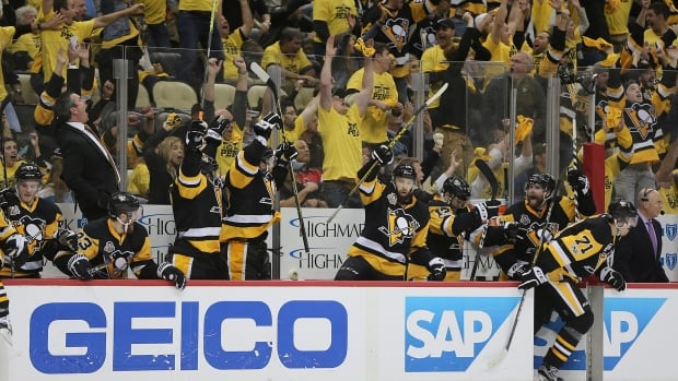 Pittsburgh Penguins players and fans celebrate as the Penguins' Chris Kunitz scores the game winning goal during the second overtime period of Game 7 against the Ottawa Senators on Thursday in Pittsburgh. The Penguins won 3-2.
