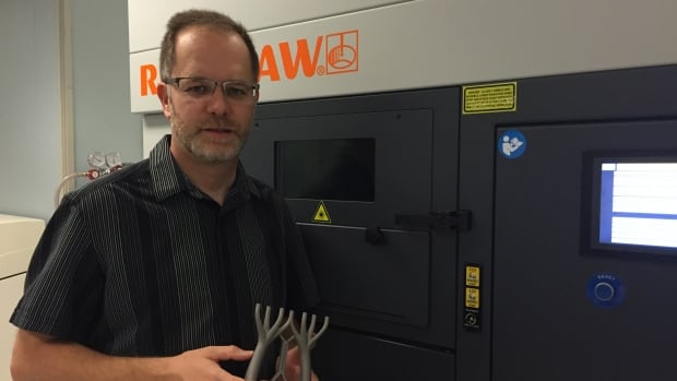 Mark Barfoot, managing director at the Multi-Scale Additive Manufacturing Lab at the University of Waterloo holds a sample 3D-printed part for a space shuttle.