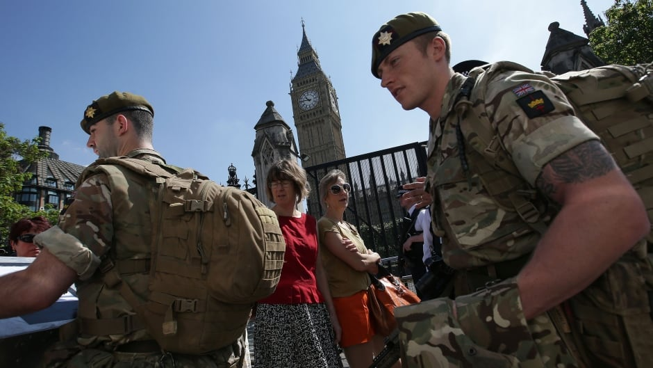 British Army soldiers patrol with police officers outside the Palace of Westminster, comprising the Houses of Parliament and the House of Lords, in central London, on May 25, 2017, following the May 22 terror attack at the Manchester Arena.