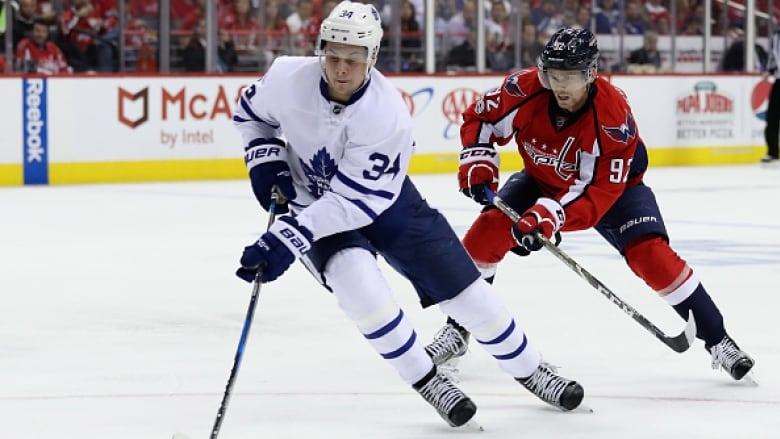Toronto Maple Leafs  Auston Matthews moves the puck in front of Evgeny  Kuznetsov of the Washington Capitals in Game 5 of their first-round playoff  series. ad0f86678cb5