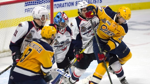 Windsor Spitfires goalie Michael DiPietro (64) keeps his eye on the puck as Erie Otters centre Warren Foegele (37) tries to deflect a shot between his legs past Spitfires defenceman Jalen Chatfield (51) during second period Memorial Cup round robin hockey action on Wednesday.