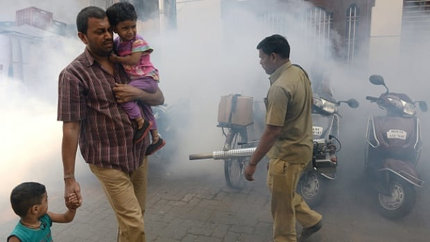 A man walks with his children as a municipal worker fumigates a residential area during a cleanliness drive in Mumbai on Feb. 25, 2016. The Zika virus, carried by the Aedes aegypti mosquito that is present in India, is believed to be linked to the serious birth defect microcephaly.