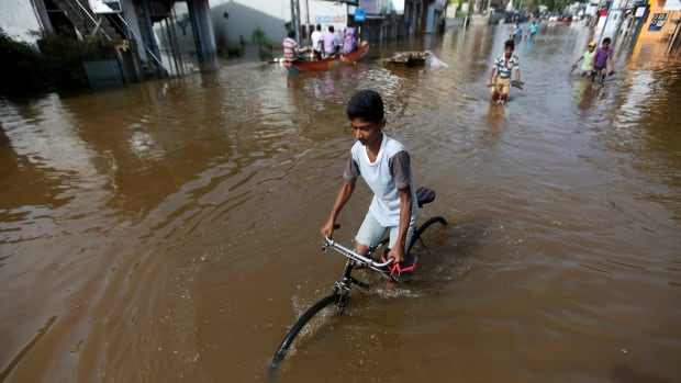 A boy rides his bike along a flooded road in Nagoda village, in Kalutara, Sri Lanka, on Monday. Floods and landslides have have killed at least 169 people in the country in recent days.