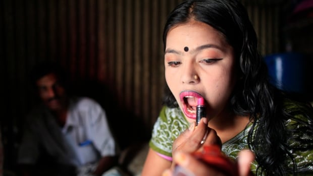 A 16-year-old prostitute applies lipstick in front of a customer inside her small room in a brothel in Tangail, Bangladesh, in March 2012. Australian pedophiles are notorious for taking inexpensive vacations in the region to abuse children.