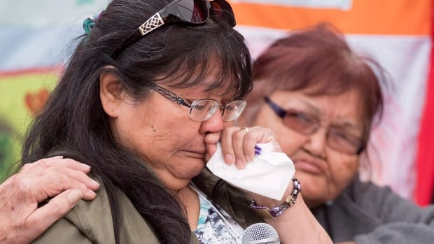 A family member looks on as May Bolton speaks about the death of her mother, Elsie Shorty, during the first public hearings of the National Inquiry into Missing and Murdered Indigenous Women and Girls in Whitehorse.