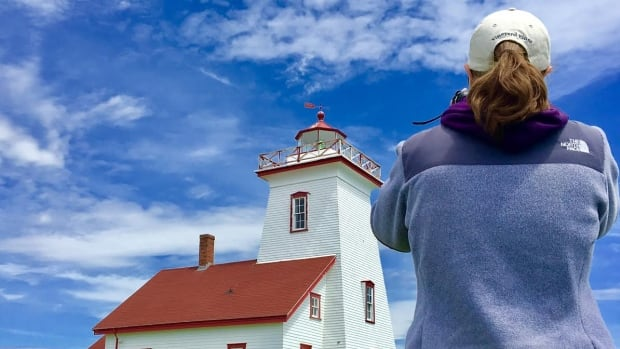 Caitlin Keller of Massachusetts takes a photo of the Wood Islands Lighthouse on her tour of the Island.