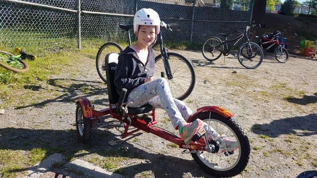 Nicole Wei sits on an adaptive tricycle. The cycle is recumbent — meaning the seat is in a laid-back position — and low to the ground.