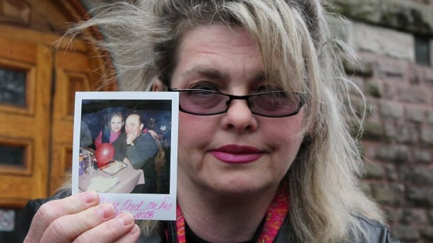 Susan Horvath, daughter of Arpad Horvath, one of former nurse Elizabeth Wettlaufer's victims, holds a photo of her father as she speaks to the media outside the court house in Woodstock, Ont., April 21.  There are calls for a public inquiry into the case.