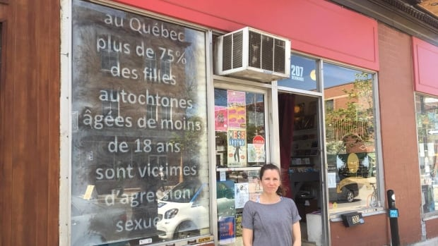 Hannah Claus stands in front of her MMIW-themed window display at Phonopolis records in Outremont, which is part of the art series Les fenêtres qui parlent. The statistic included in the display translates to, 'In Quebec, more than 75 per cent of Indigenous women under the age of 18 are victims of sexual assault.'