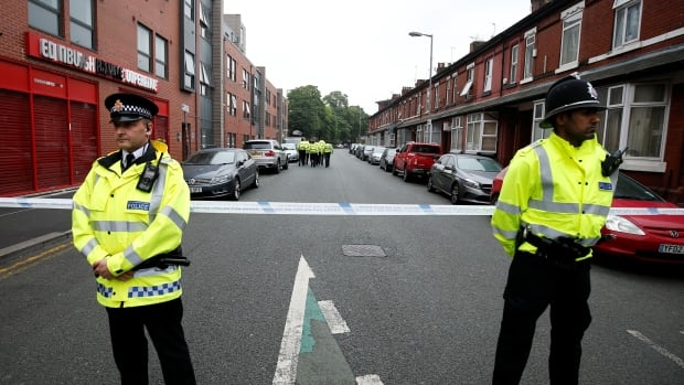 Police stand in front of an area cordoned off in Manchester Friday as police investigated a vehicle that could be linked to suicide bomber Salman Abedi.