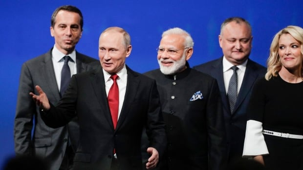 Russian President Vladimir Putin arrives to address the St. Petersburg International Economic Forum in St. Petersburg, Russia on Friday. To his left is Austrian Chancellor Christian Kern and on the right is India's Prime Minister Narendra Modi, Moldovan President Igor Dodon and NBC journalist Megyn Kelly.