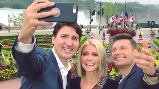 Prime Minister Justin Trudeau snaps a selfie with morning show hosts Kelly Ripa and Ryan Seacrest in Niagara Falls, Ont. on Monday.