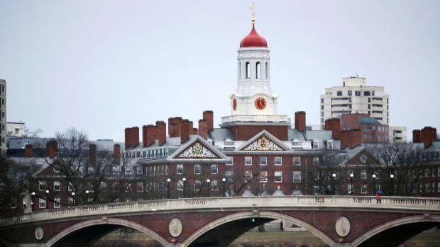 In this March 7, 2017 file photo, rowers paddle along the Charles River past the Harvard College campus in Cambridge, Mass. The Harvard Crimson, the school's student newspaper, reported June 4, 2017, that Harvard revoked admission offers to at least 10 prospective freshmen over offensive online messages.