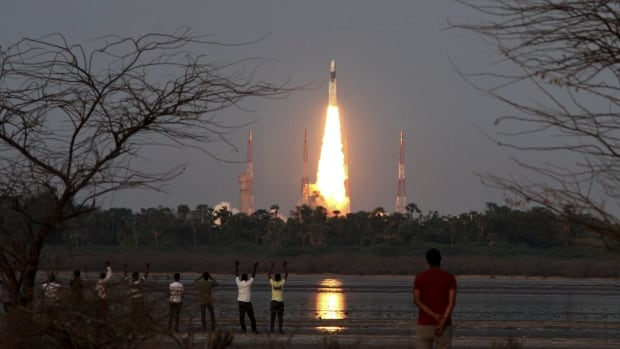 People watch as Indian Space Research Organization's Geosynchronous Satellite Launch Vehicle Mk III rocket lifts off from the space launch centre in Sriharikota, India.
